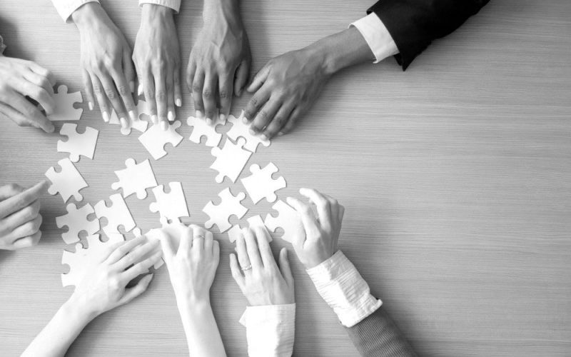 hands-of-multiethnic-business-team-assembling-jigsaw-puzzle-top-view-min