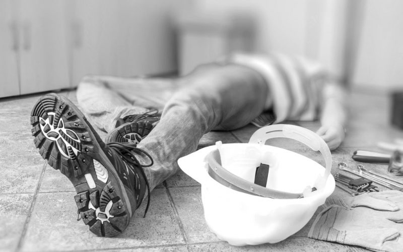 leg-and-yellow-helmet-of-injured-lying-worker-at-work-min